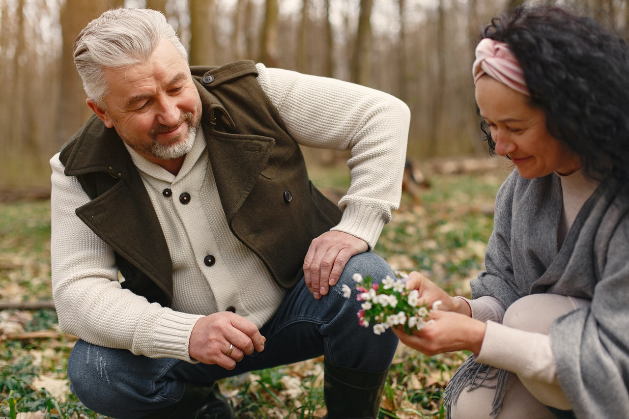 Older man and woman picking flowers in a field.